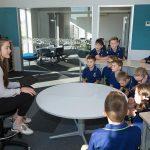 Knights Stream School students seated around a circular desk with female teacher